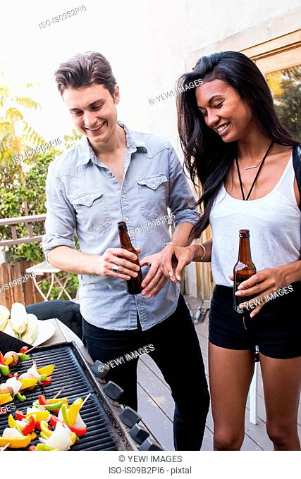 Young couple outdoors, holding beer bottles, cooking food on barbecue
