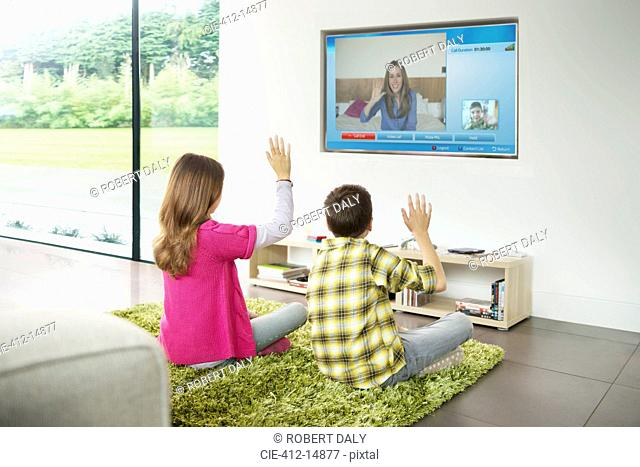 Children video chatting on television in living room
