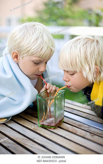 Two brothers drinking syrup with straws, Sweden