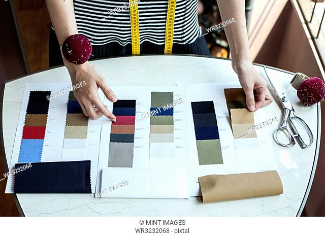 High angle close up of fashion designer working in her studio, looking at fabric samples