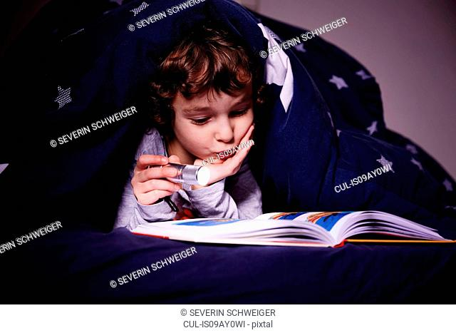 Boy underneath duvet reading book by torchlight