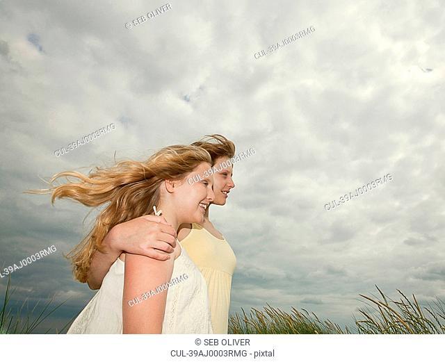 Girls hugging under cloudy sky