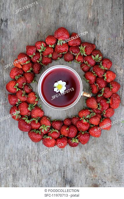 A cup of strawberry tea surrounded by fresh strawberries (seen from above)
