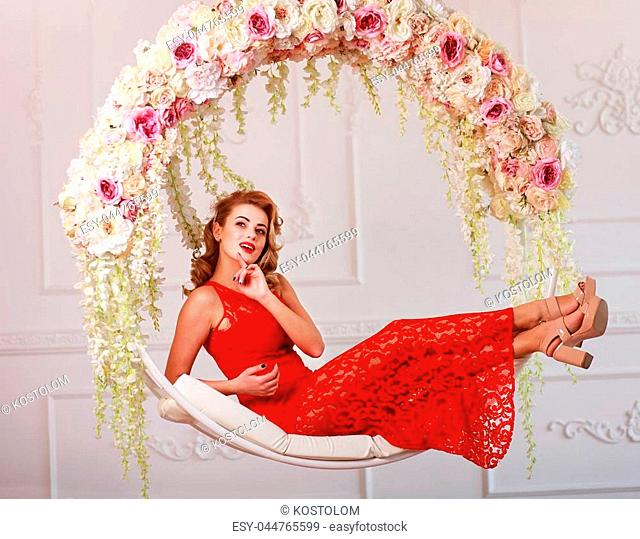 Joyful elegant woman in a red dress on a swing in flowers