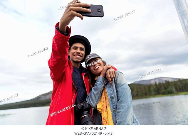 Finland, Lapland, happy couple taking a selfie at a lake