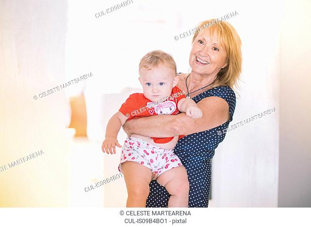 Portrait of senior woman carrying baby granddaughter at home