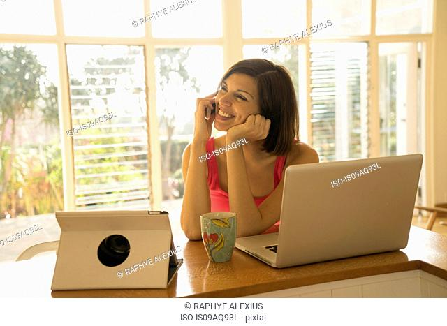 Businesswoman chatting on smartphone whilst using laptop in living room