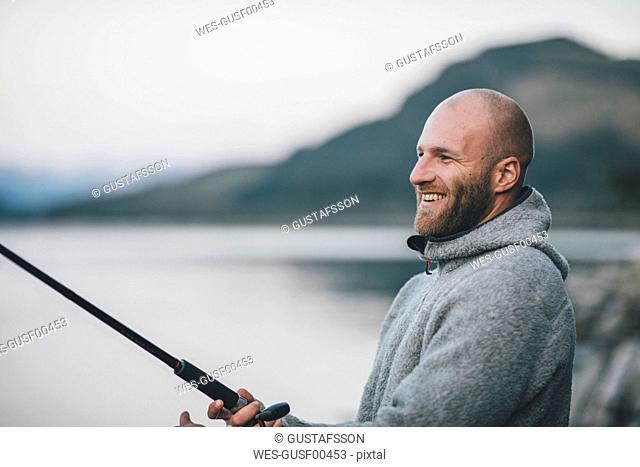 Canada, British Columbia, happy man fishing at Kinbasket Lake