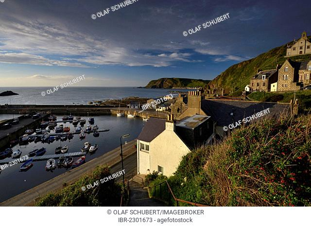 Houses and the harbor with small fishing boats off the cliff coast in Gardenstown, Banffshire, Scotland, United Kingdom, Europe