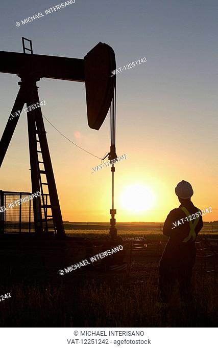 Silhouette of pump jack and oil worker with hard hat and protective coveralls with orange sunrise in background and blue sky; Alberta, Canada
