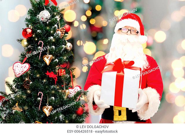 christmas, holidays and people concept - man in costume of santa claus with gift box and tree over lights background