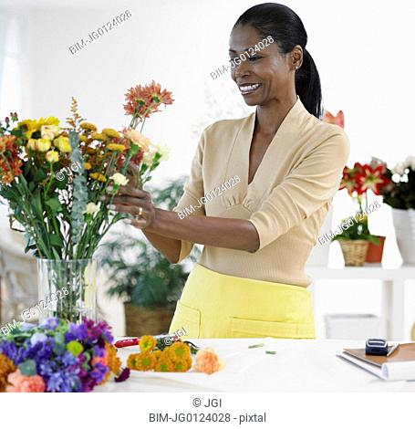 African female florist arranging flowers in shop
