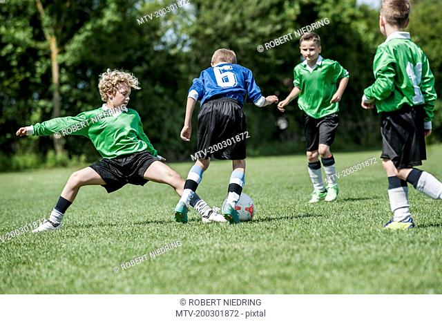 Junior boys football soccer game sliding tackle