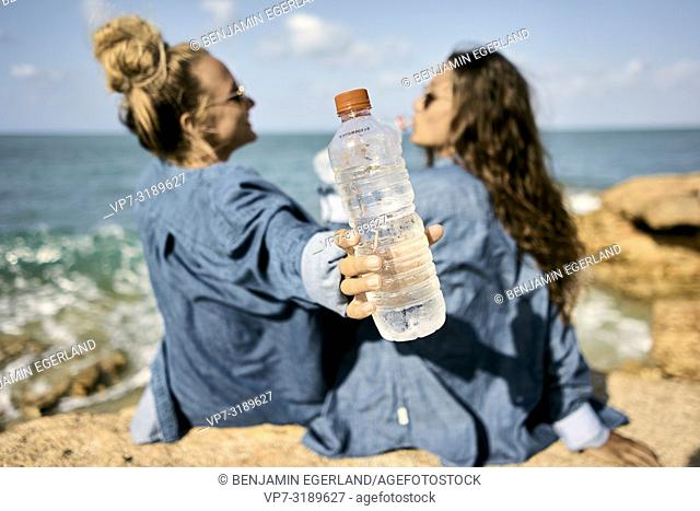 Two women sitting at beach, Chersonissos, Crete, Greece