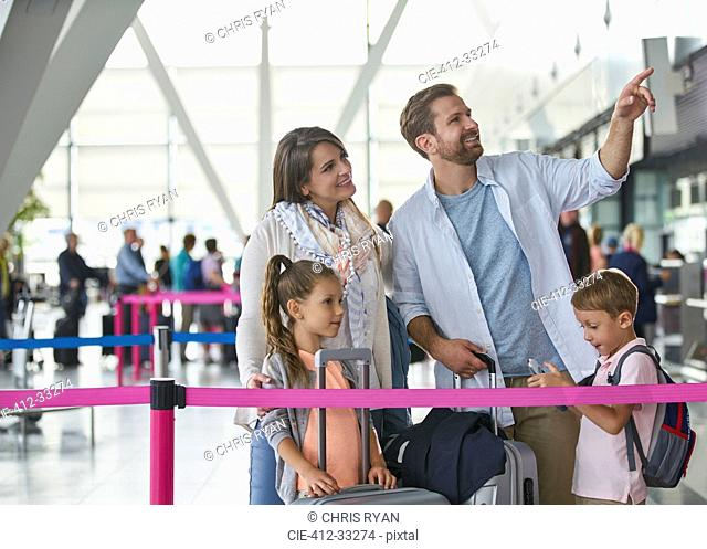 Family with suitcases pointing in airport concourse