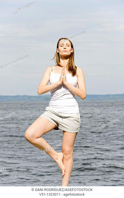 Portrait of a brunette woman doing yoga by the sea