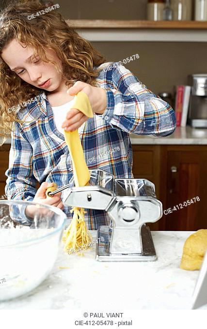 Girl rolling pasta dough in kitchen