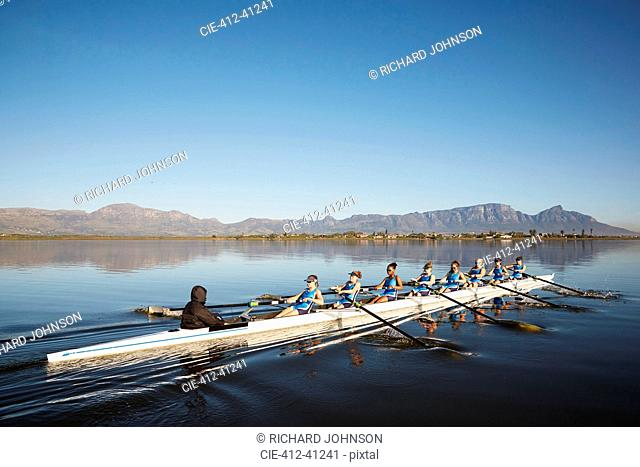 Female rowers rowing scull on sunny lake under blue sky
