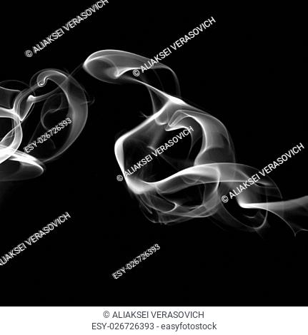Abstract white smoke swirls on black background