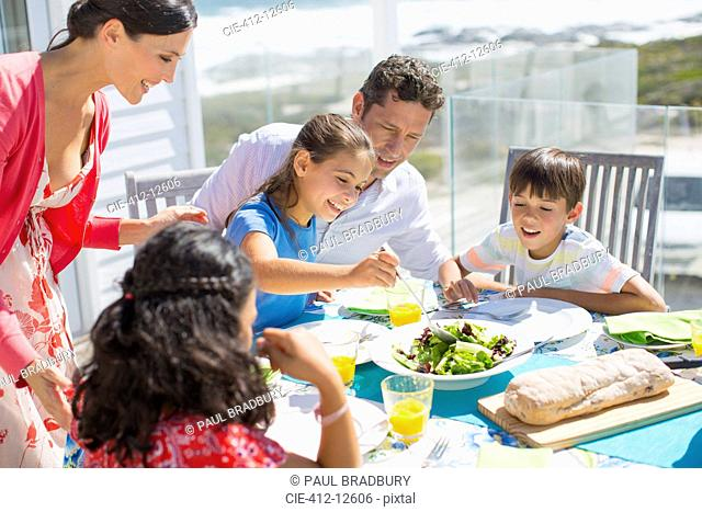 Family eating lunch at table on sunny patio