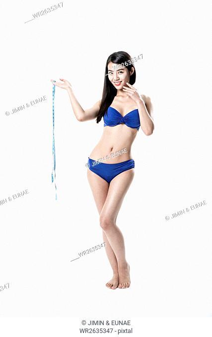 Young smiling slim woman in bikini posing with tape measure