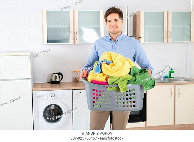 Young Handsome Man Carrying Basket With Heap Of Clothes In Kitchen