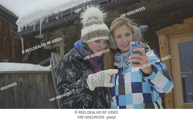 Young women enjoying in winter and taking selfie in snow