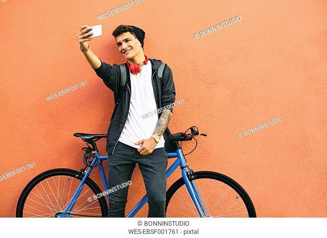 Teenager with a fixie bike, selfie, smartphone