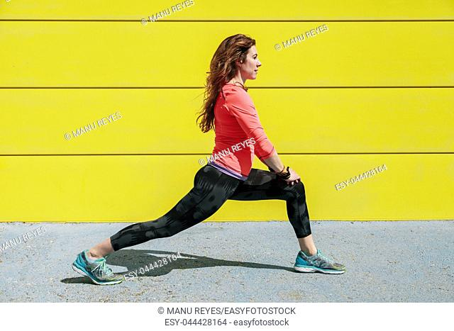 young woman stretching on the floor in front of a yellow wall before running
