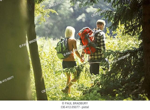 Couple with backpacks holding hands hiking in sunny woods