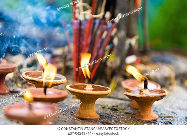 Terra-cota oil lamps as religious offerings at temple in Nepal. Incence sticks over blurred background