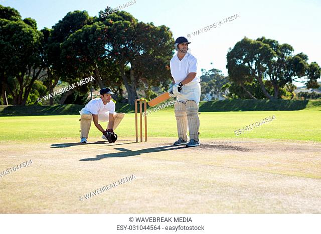 Men playing cricket at pitch against clear sky