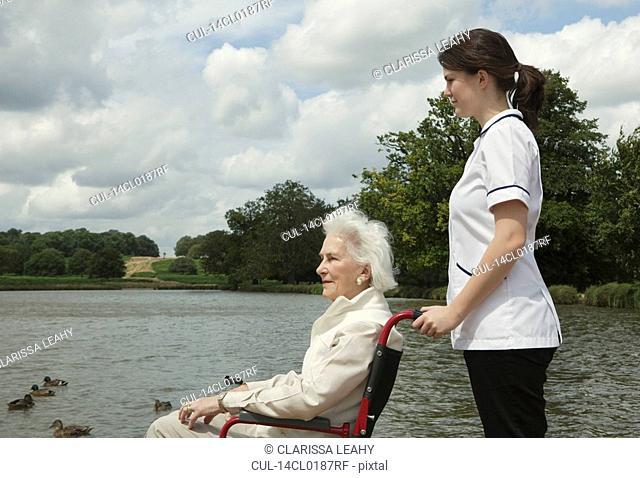 Elderly woman in wheelchair with nurse