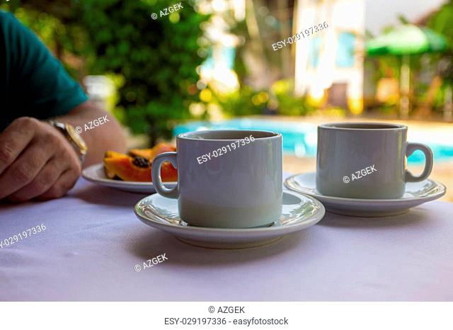 Breakfast - two cups of coffee, rolls and papaya on the pool background