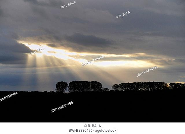 last sunbeams in front of a storm front, Germany