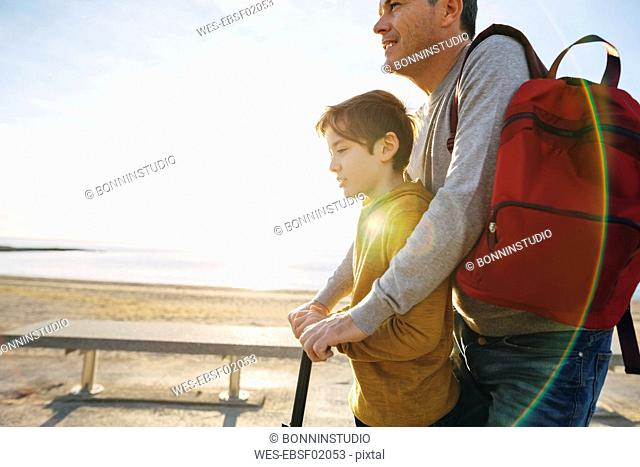 Father and son with scooter on beach promenade at sunset