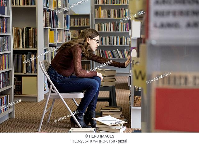 Bookstore worker with clipboard checking inventory