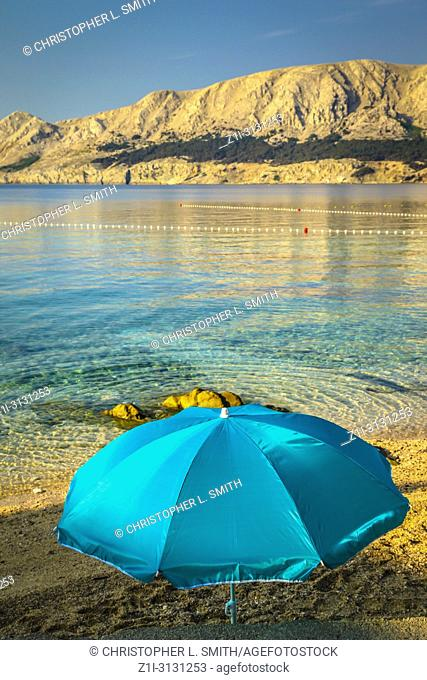 A lone umbrella on the beach at daybreak at the waters edge of the adriatic at Baska on the island of Krk