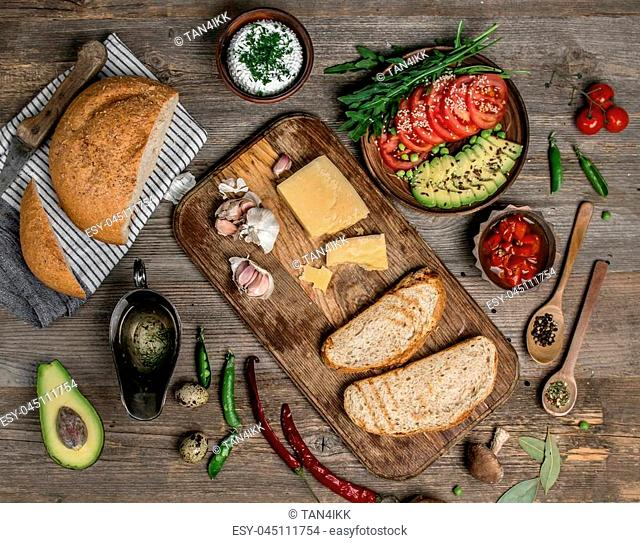 Avocado, cheese, bread and tomatoes, appetizing foods served on wooden table, topview