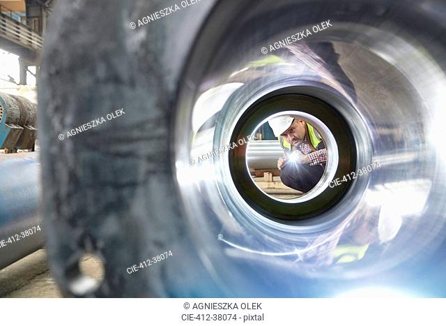 Male engineer with flashlight examining steel pipe in factory