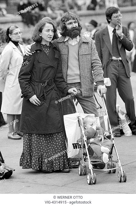 GROSSBRITANNIEN, LONDON, 02.06.1979, Seventies, black and white photo, people, family, parents and a baby in a buggy stand on a square and watch an event, man
