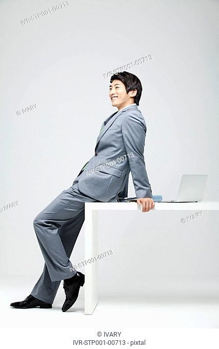 Portrait Of Smiling Asian Businessman Leaning On Desk, Laptop And File On Desk