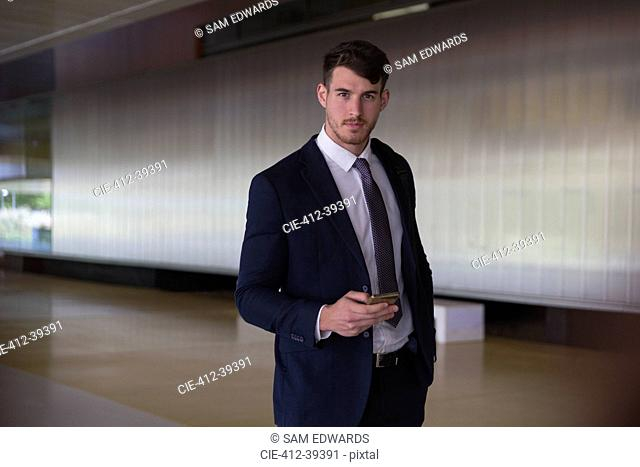 Portrait confident, serious businessman texting with smart phone in office lobby
