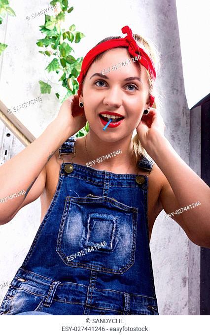 beautiful young woman in denim overalls and a bandana looking at the camera as the mirror, Chupa Chups licking and posing