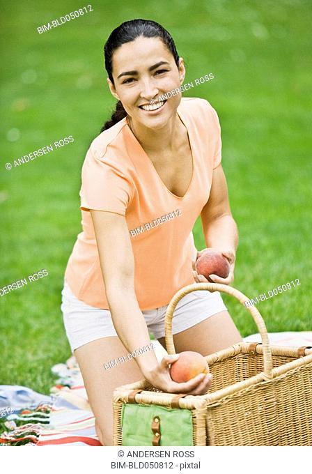 Hispanic woman unpacking picnic basket
