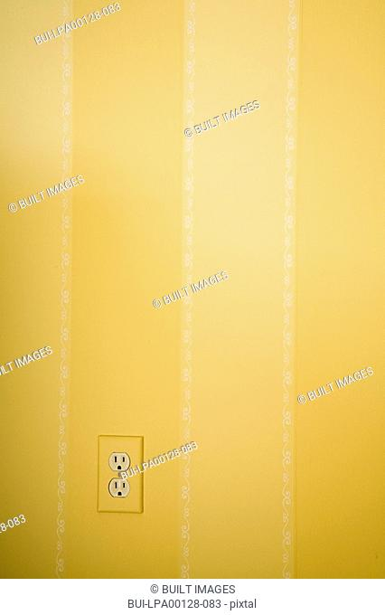 Yellow striped wall with electrical outlet