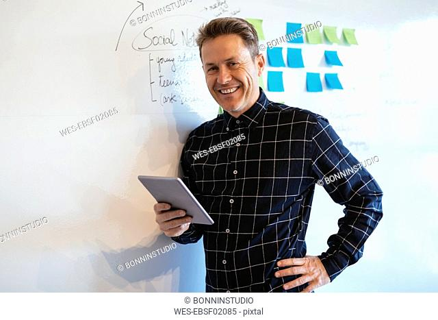 Smiling businessman with tablet in office leaning against whiteboard