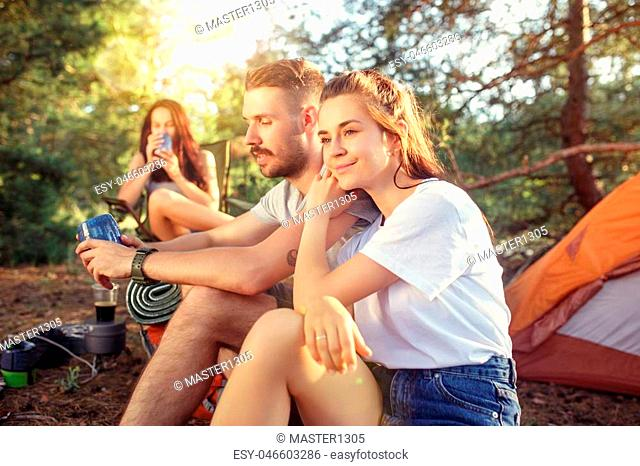 Party, camping of men and women group at forest. They relaxing against green grass. The vacation, summer, adventure, lifestyle, picnic concept