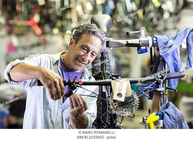 Caucasian man repairing brakes on bicycle