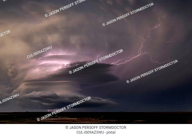 Powerful electrical storm with lightning arcing out of the updraft into the anvil and a cloud-to-ground bolt shooting out of the bottom of the rotating...